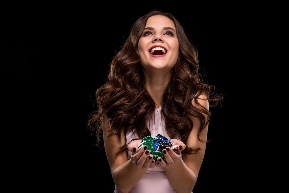 gagnante de casino en ligne heureuse avec des jetons en main