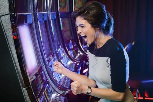 jeune femme heureuse qui joue aux machine à sous dans un casino