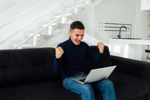 jeune homme heureux de ses gains assis sur un sofa avec son ordinateur portable sur les genoux