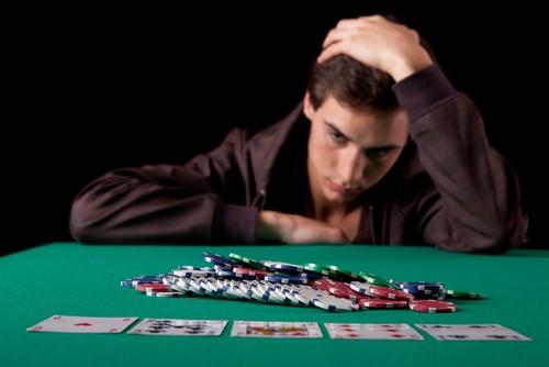 joueur de poker avec une multitude de jetons de casino ayant l'air abbatu