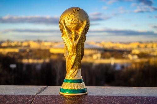illustration de la coupe du monde posée sur le rebor d'un mur surplombant une ville