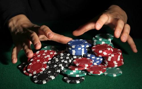 mains d'homme s'accaparant une pile de jetons de casino