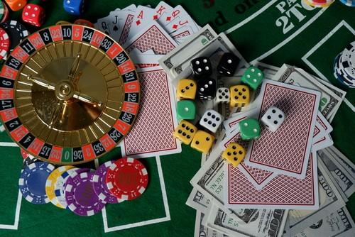table de jeu avec une roulette, un jeu de cartes, des jetons, des dés et de l'argent liquide