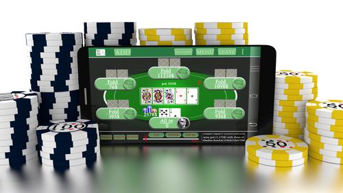 tablette informatique diffusant un jeu de casino et entouré d'une multitude de jetons