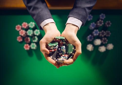 homme élégant tenant dans sa main des jetons de casino au-dessus d'une table sur laquelle sont disposés d'autres jetons