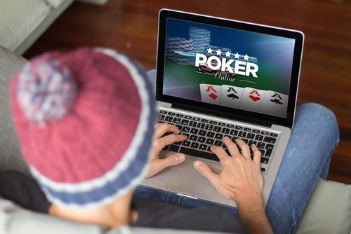 jeune homme jouant au poker en ligne depuis son ordinateur sur son sofa